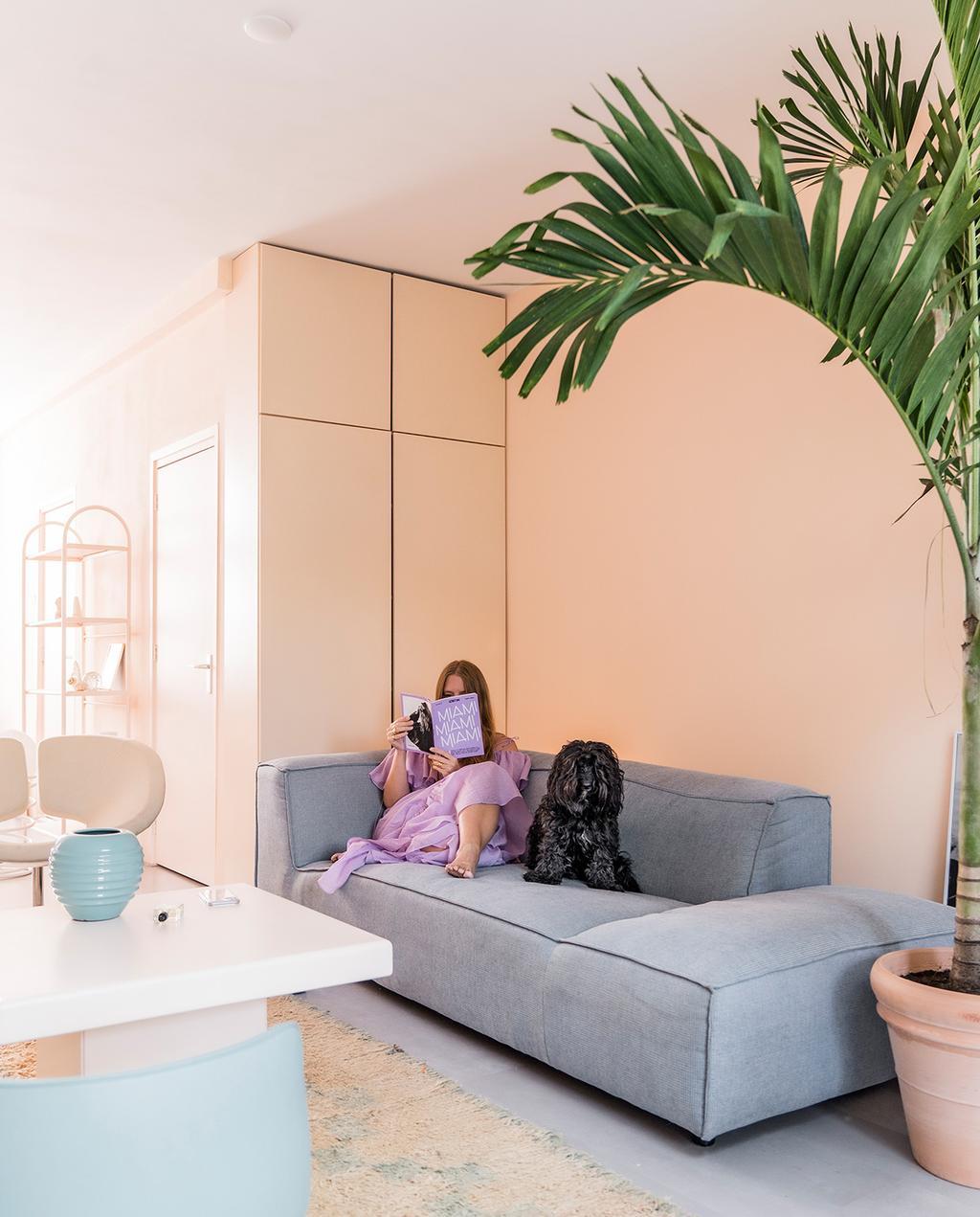 vtwonen special tiny houses 03-2021 | grijze bank in wevershuis met witte tafel en pastel oranje kleur muren