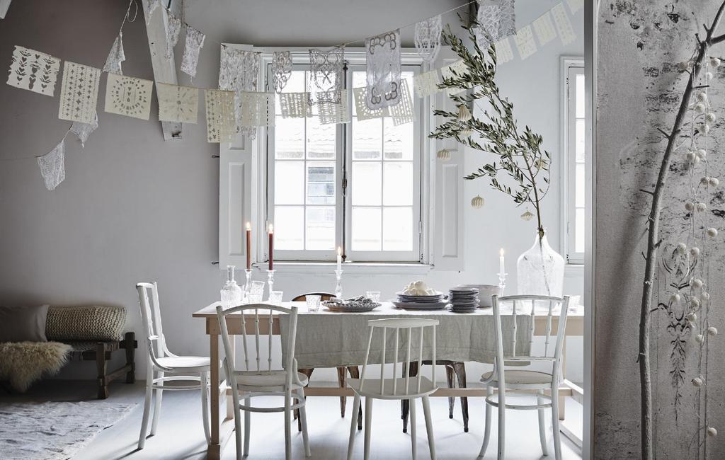 Papieren slingers boven een kersttafel in wit