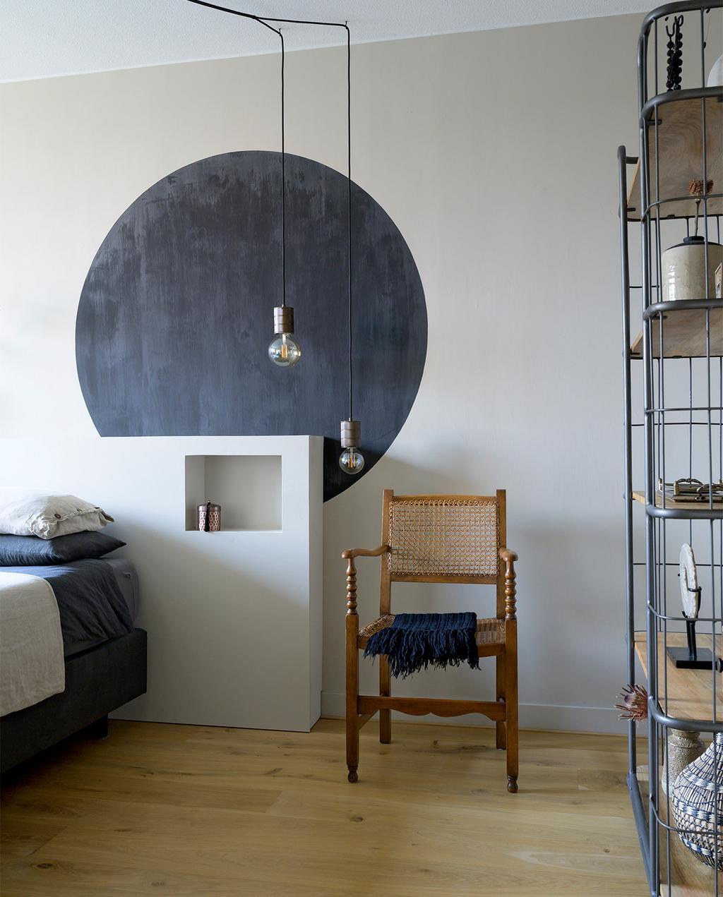 vtwonen 08-2021   zwarte ronde cirkel op de wand achter het bed in de slaapkamer met rieten stoel, een wit hoofdbord en een open kast