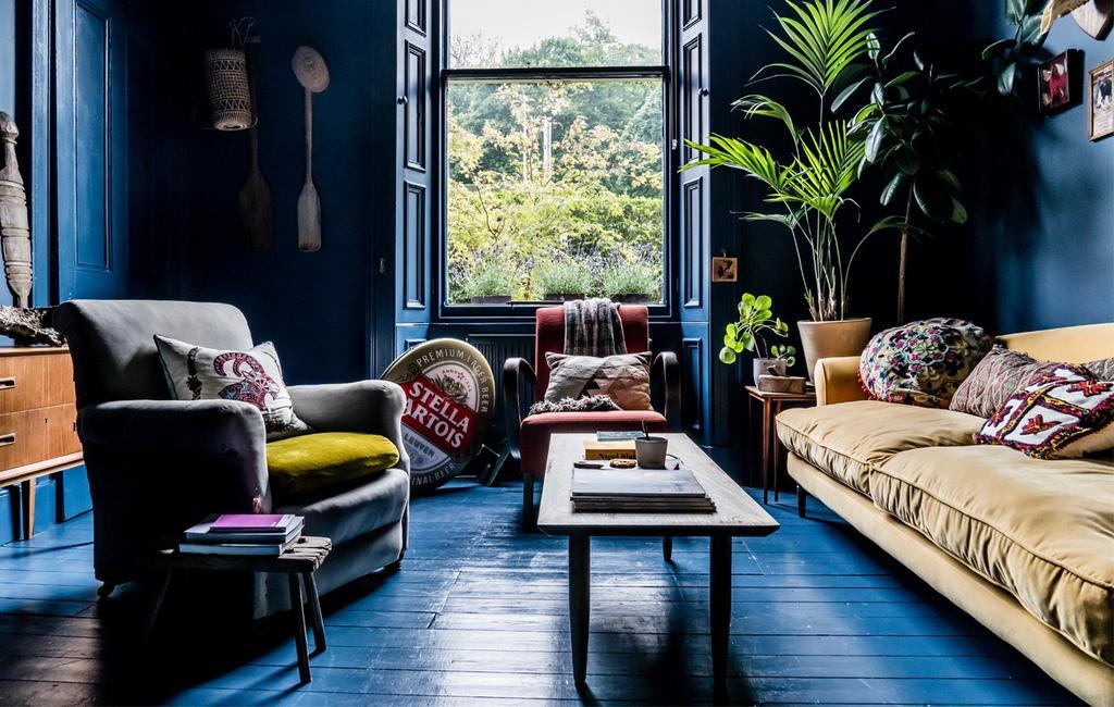 donkerblauwe woonkamer in Edinburgh, met een okergele zetel en grijze stoel