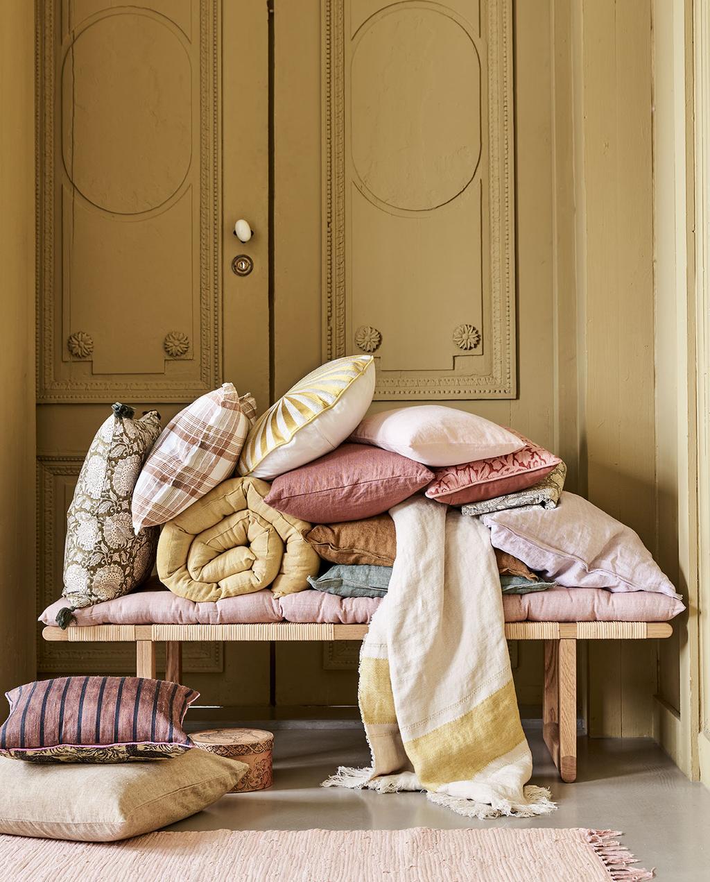 vtwonen 05-2021 | verschillende gekleurde kussens en dekens op een houten bank
