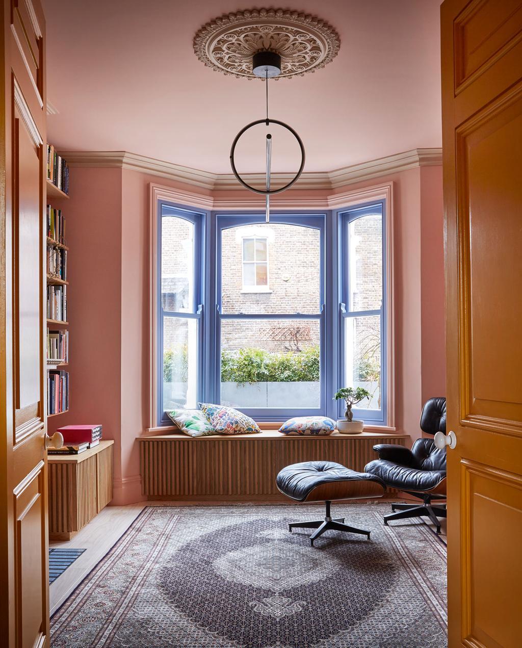 vtwonen 05-2020 | styling colourboost woonkamer met roze muren en paarse kozijnen en zwarte eames fauteuil