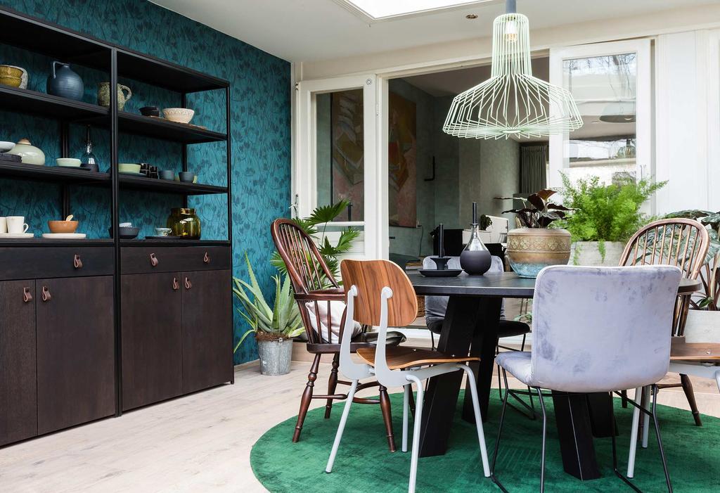 Serre met daarin een ronde eettafel en zwarte boekenkasten tegen blauw behang