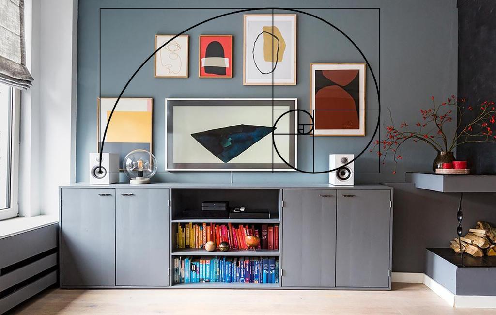 grijze fotowand met verschillende printen en boeken op kleur ingedeeld