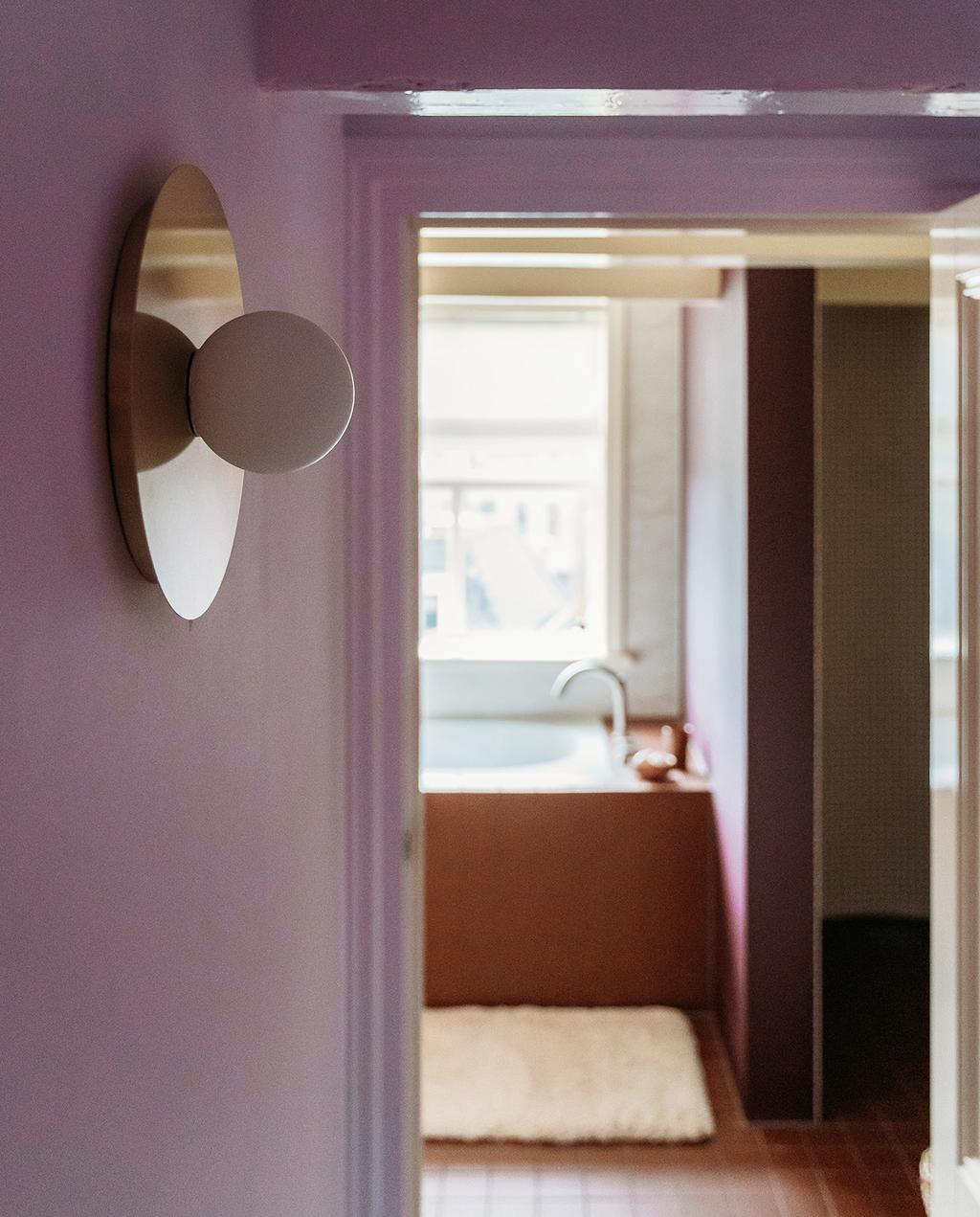 vtwonen 03-2021 | roze hal met muur en deur naar de badkamer