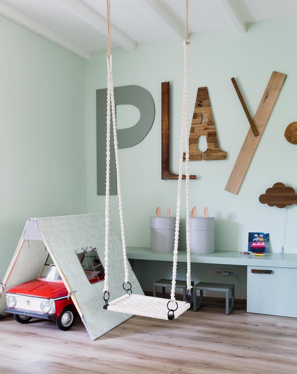 Speelhoek met schommel, tent en houten letters