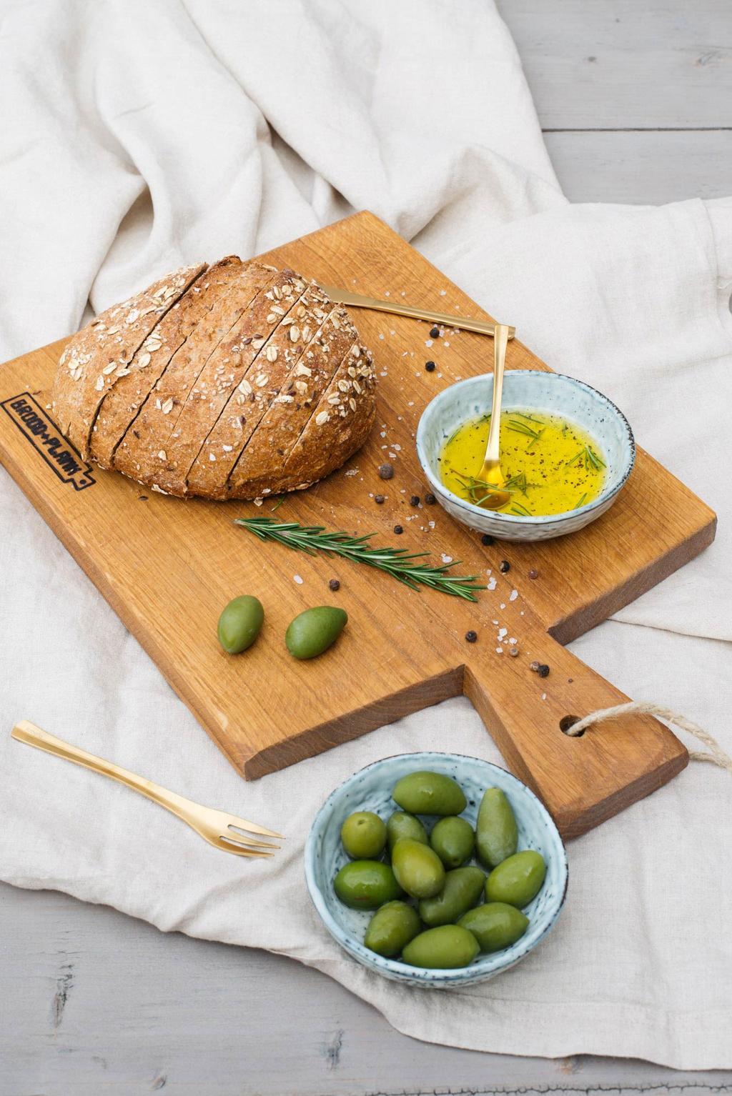 Broodplank met brood, olijven en olijfolie in het voorjaarshuis van REMADE with love