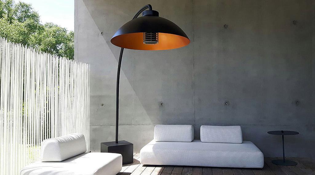 De terrasverwarmer van Hanolux op een terras met witte zetels voor een grijze muur