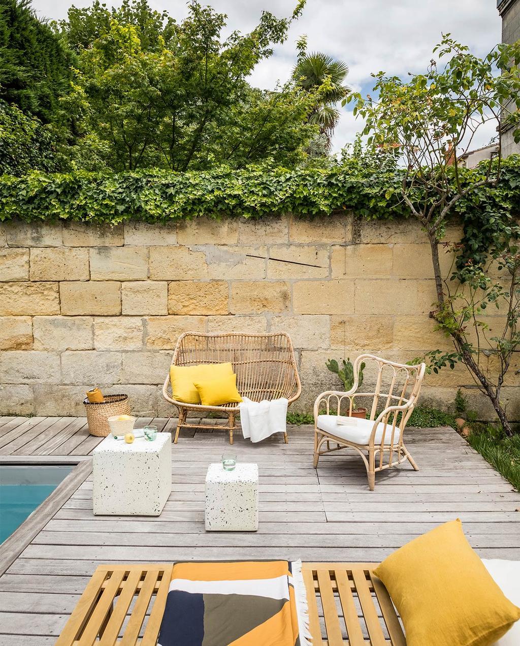 vtwonen special zomerhuizen 07-2021 | tuinbank bij het zwembad met okergele kussens