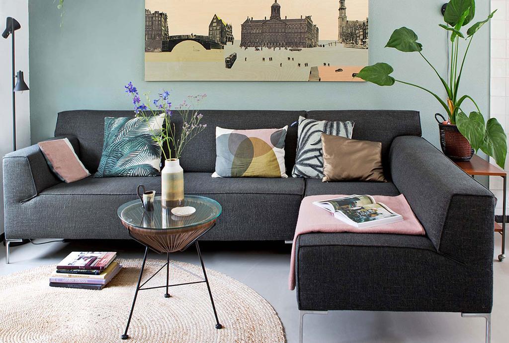 Grijze bank in de zithoek tegen gekleurde wand in een herenhuis in Amsterdam