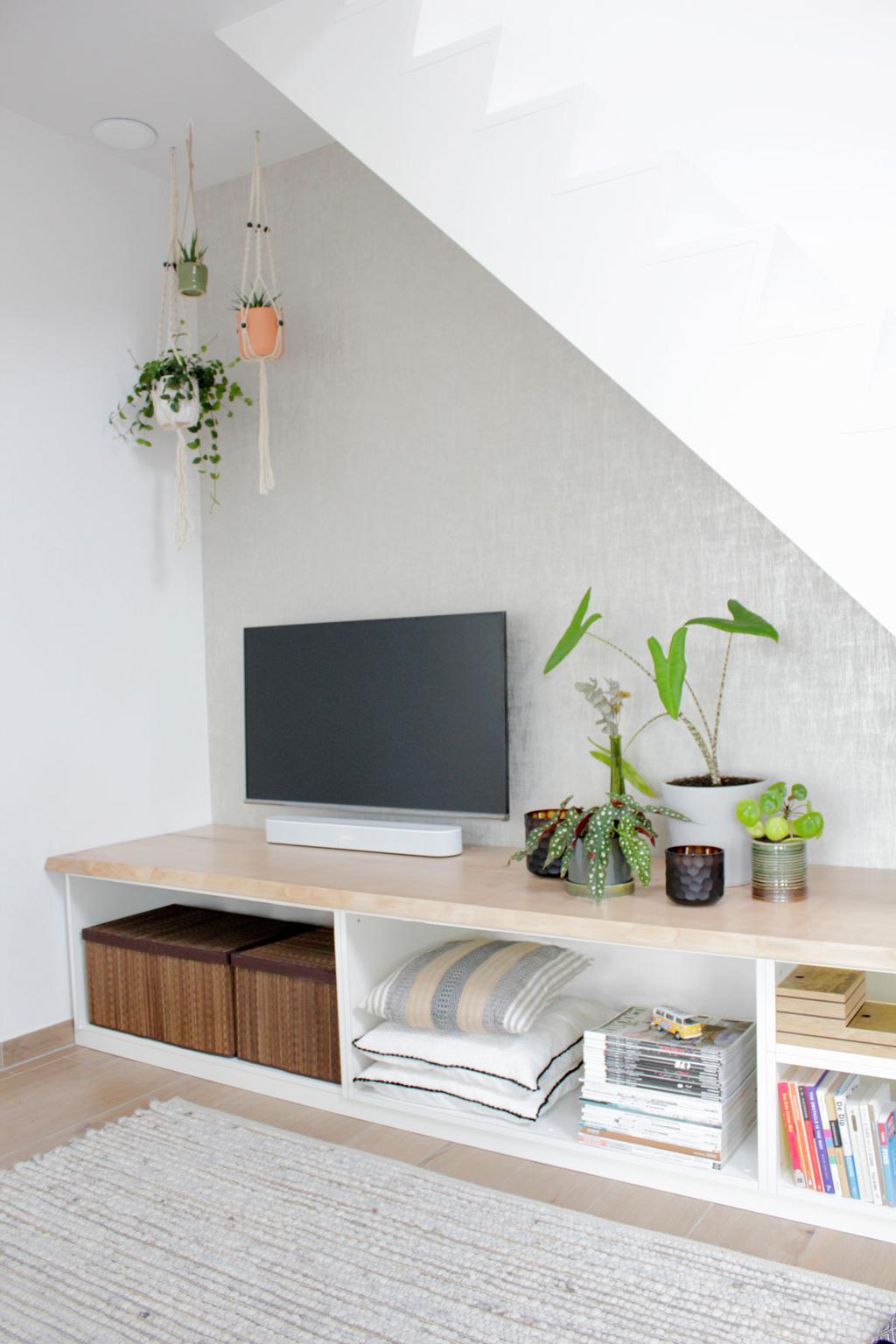 Ingebouwde trapkast met televisie en groene planten voor een witte muur