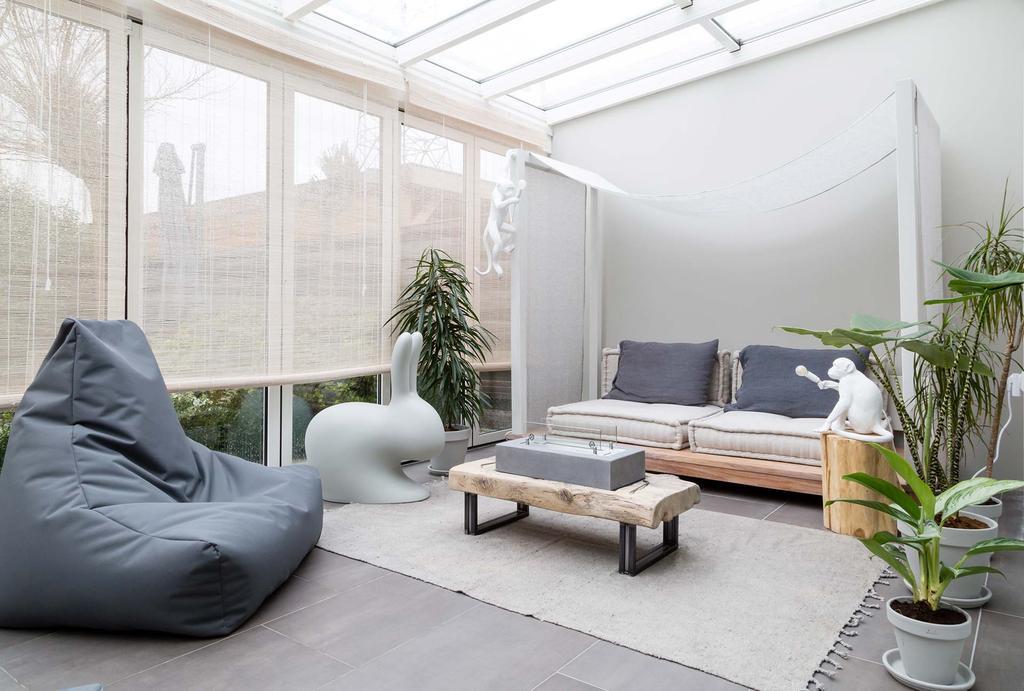Loungehoek in de serre met loungebank van hout en grote zitzakken