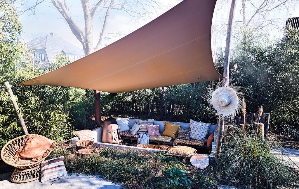 vtwonen tuin special 2 2020 | buitenplaats gedecoreerde buitenbank met kussens en zonwering mediterraanse tuin styling