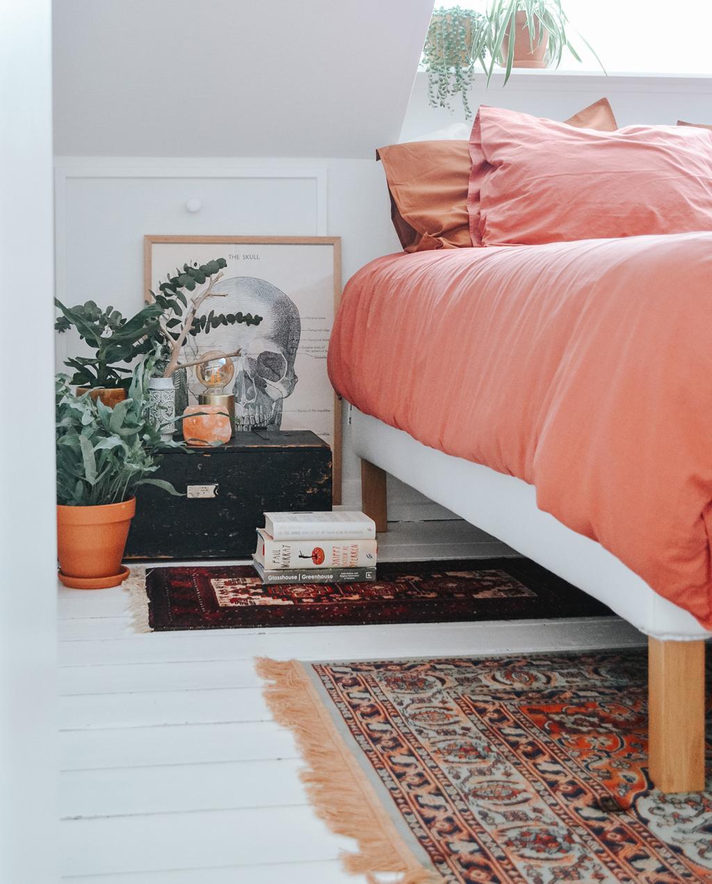 bed in bohemian slaapkamer met terra dekbed en planten