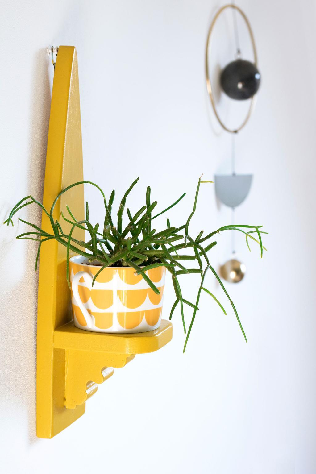 Gele wandplank met een plant in een gele bloempot