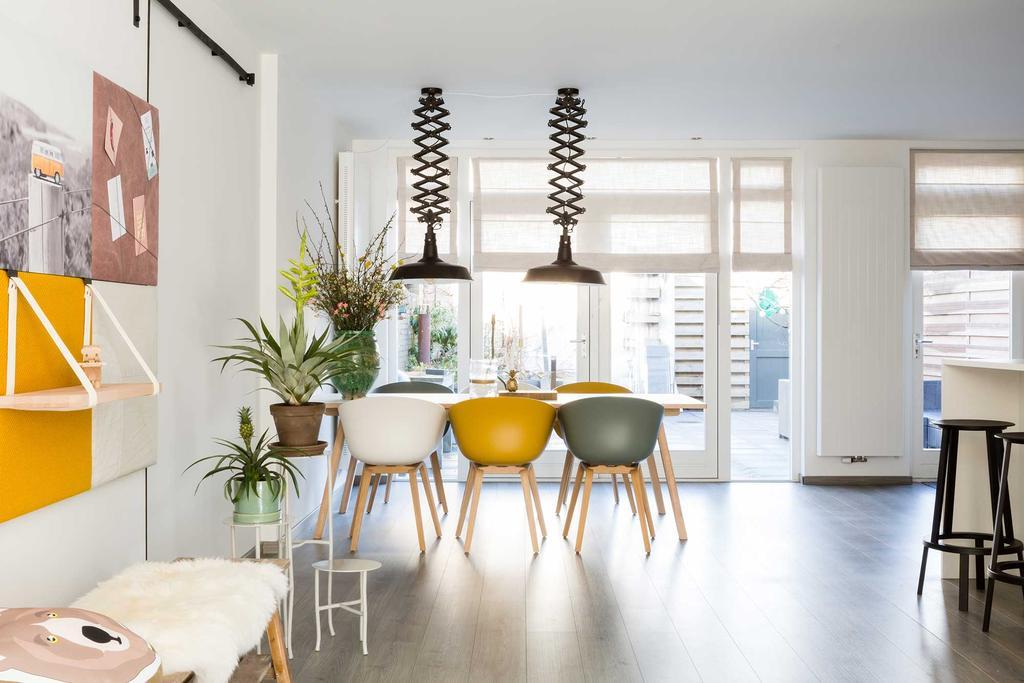 Eethoek met verschillende kleuren eetkamerstoelen en industriële hanglampen
