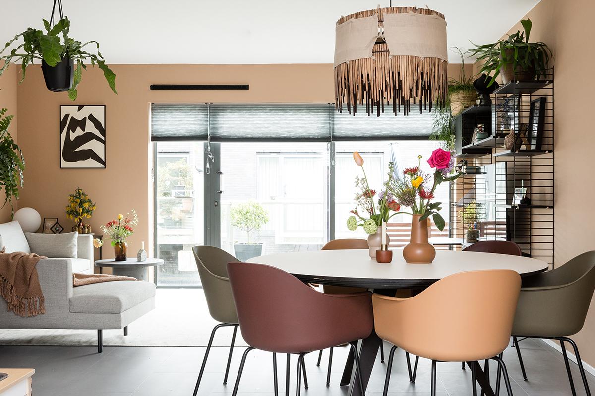 Woonkamer met eettafel met gekleurde stoelen en daarboven een hanglamp