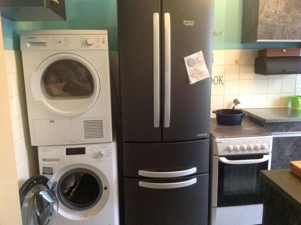 de-oude-keuken-met-wasmachine-droger-koelkast-en-gasfornuis