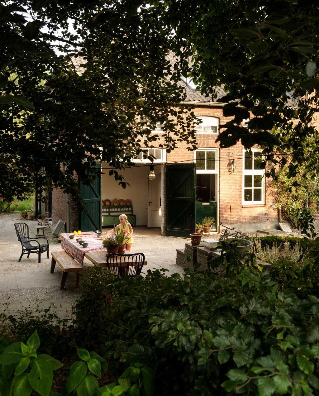 vtwonen 10-2020 | Kijkkamer bommelerwaard | tuin met openslaande schuurdeur en een gedekte tafel