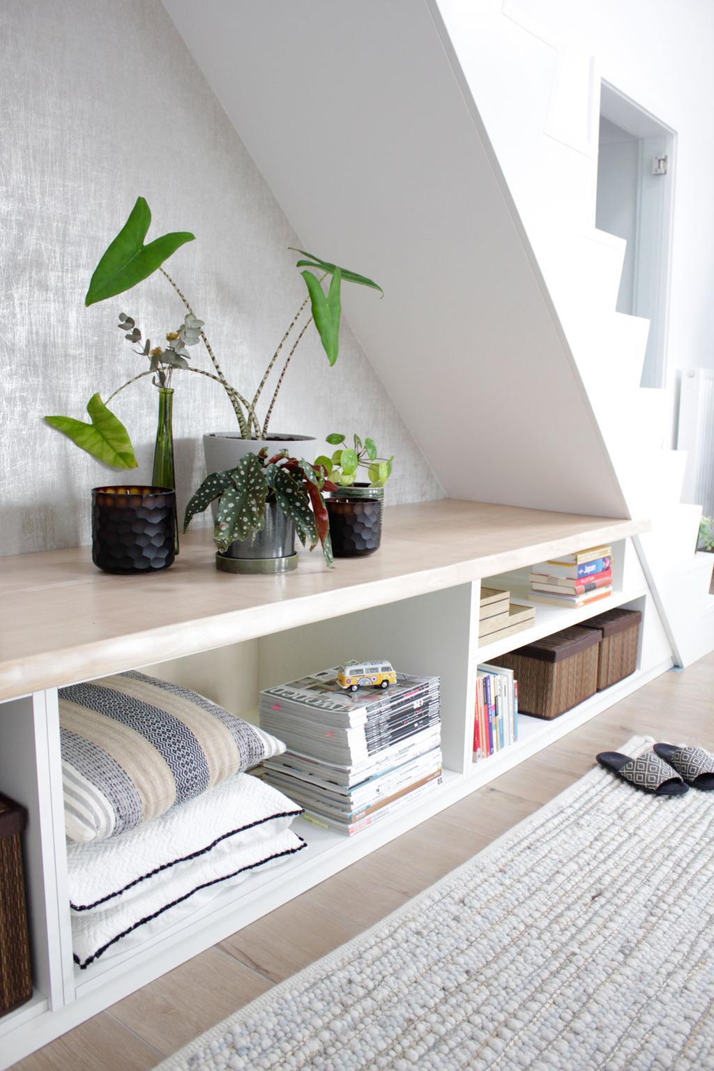 Ingebouwde kast met houten afwerking en groene accessoires voor witte muur