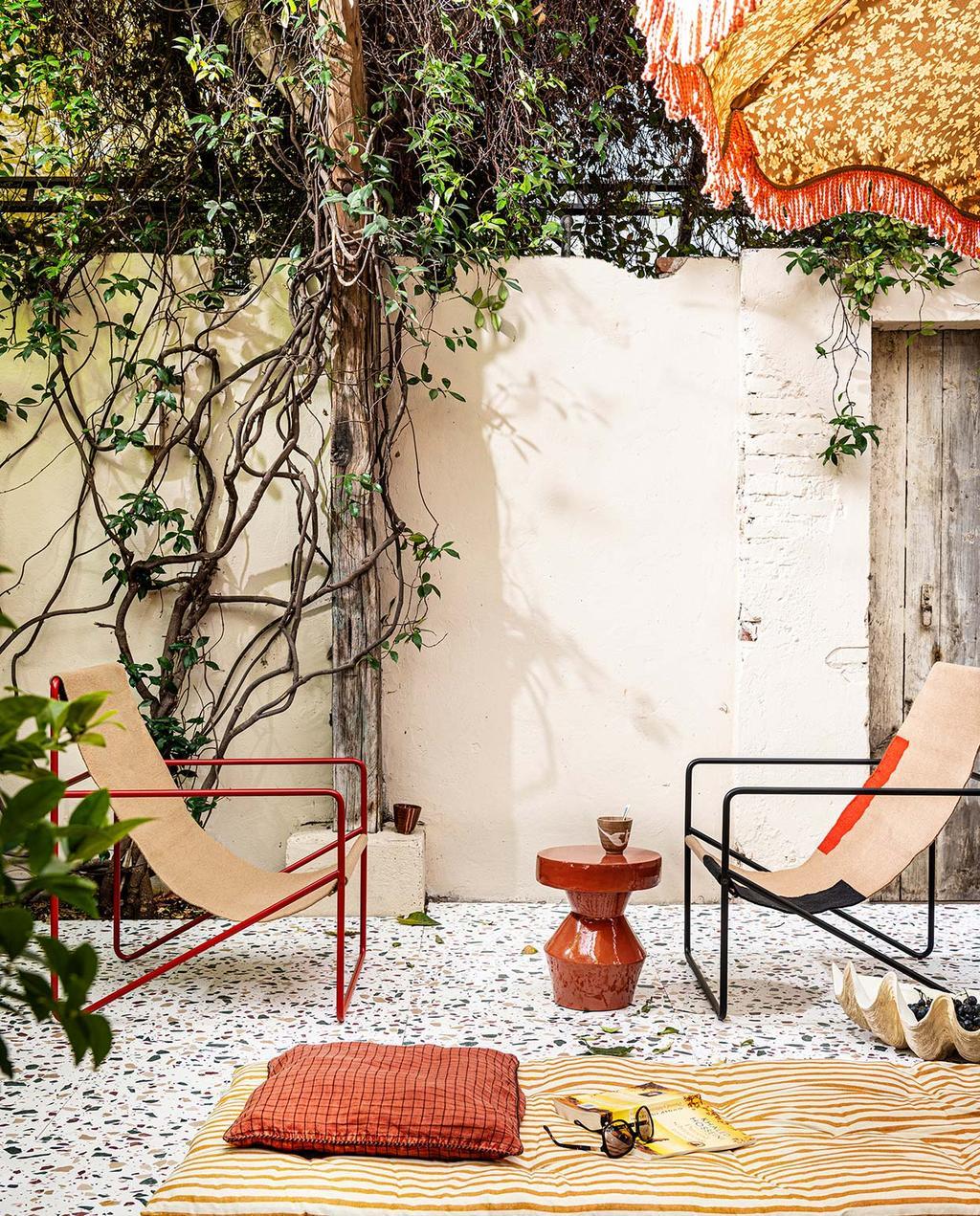 vtwonen 07-2021 | twee bijzondere stoelen met een rode bijzettafel in de tuin