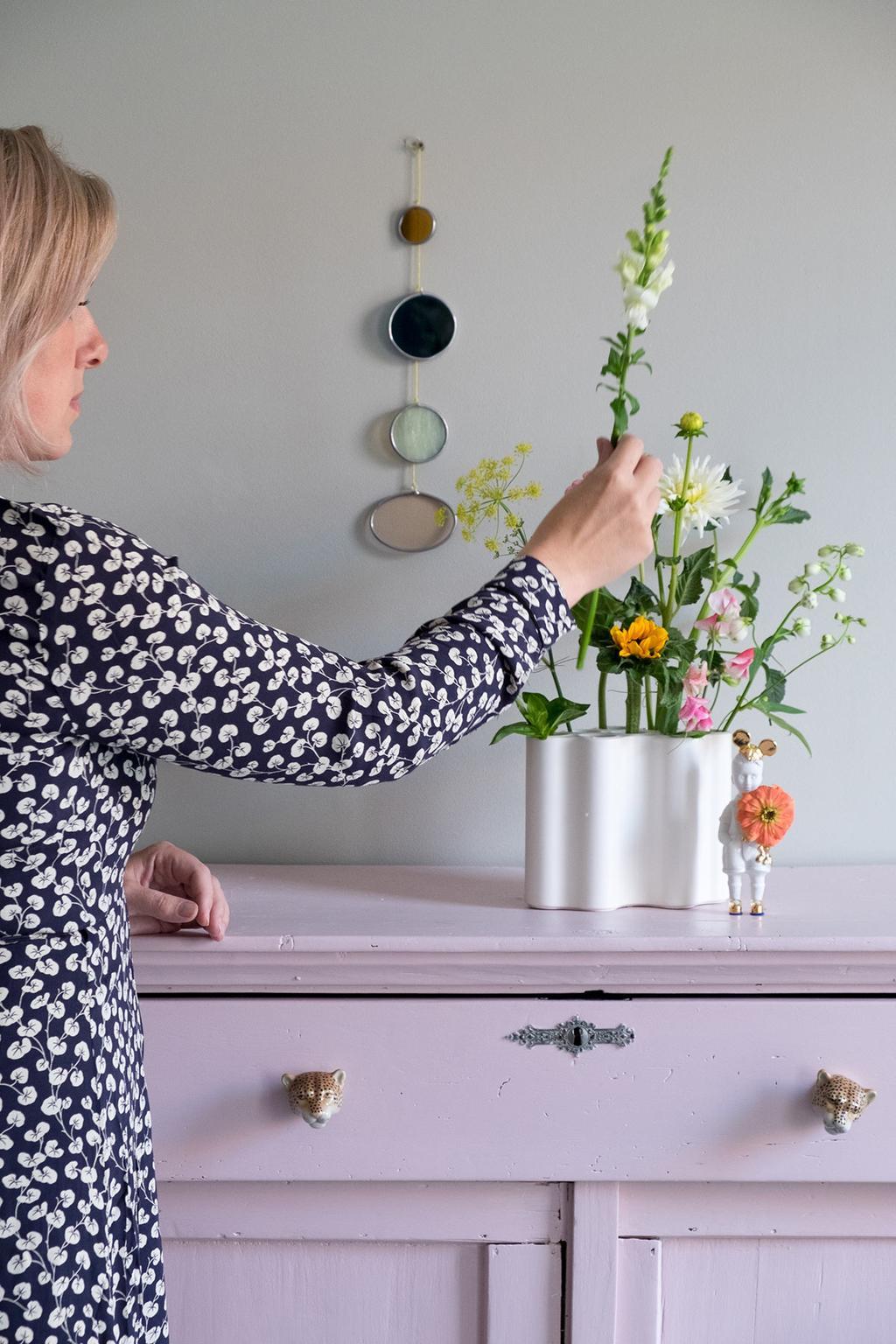 Glas-in-lood van De Glazerij boven een roze dressoir met bloemen