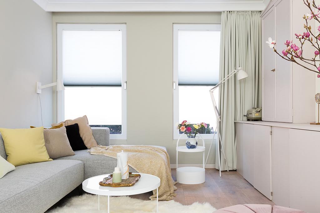 Woonkamer met een grijze bank en lichte kleuren