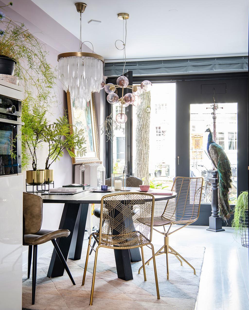 vtwonen 06-2021 | kamer met ronde tafel en gouden stoelen en kandelaar