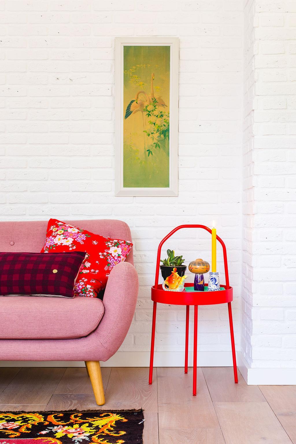Roze bank en rood tafeltje met chinoiserie en kokeshi