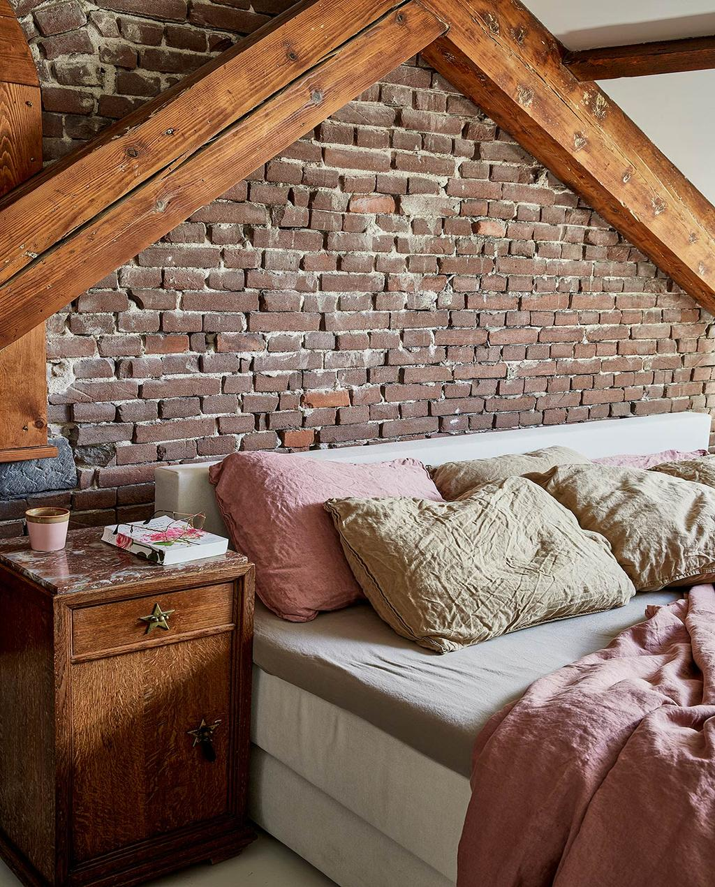 vtwonen 02-2021 | binnenkijken bij Martine stenen muur in slaapkamer met een opgemaakt roze bed