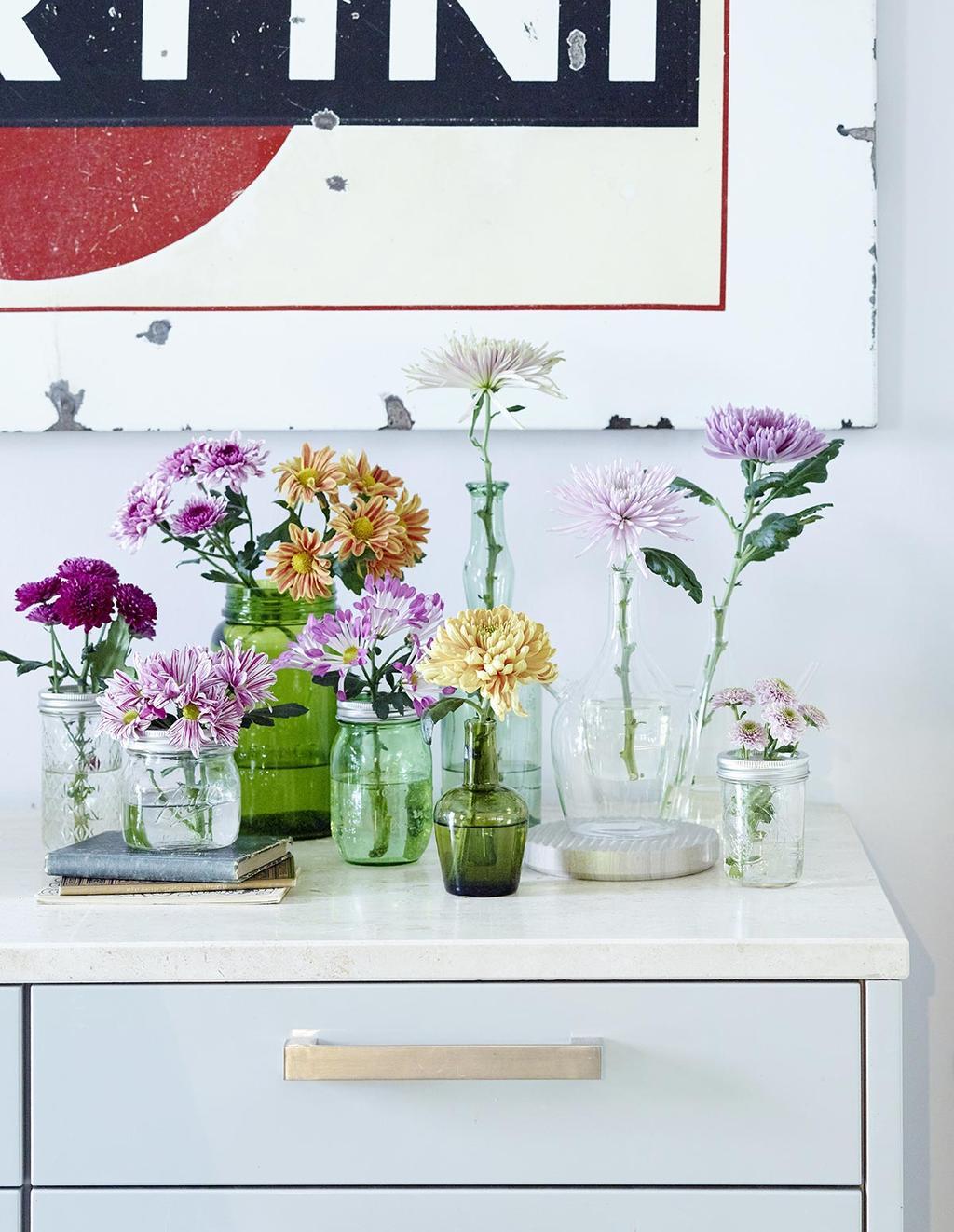 Chrysanten in glazen vazen op een ladekastje