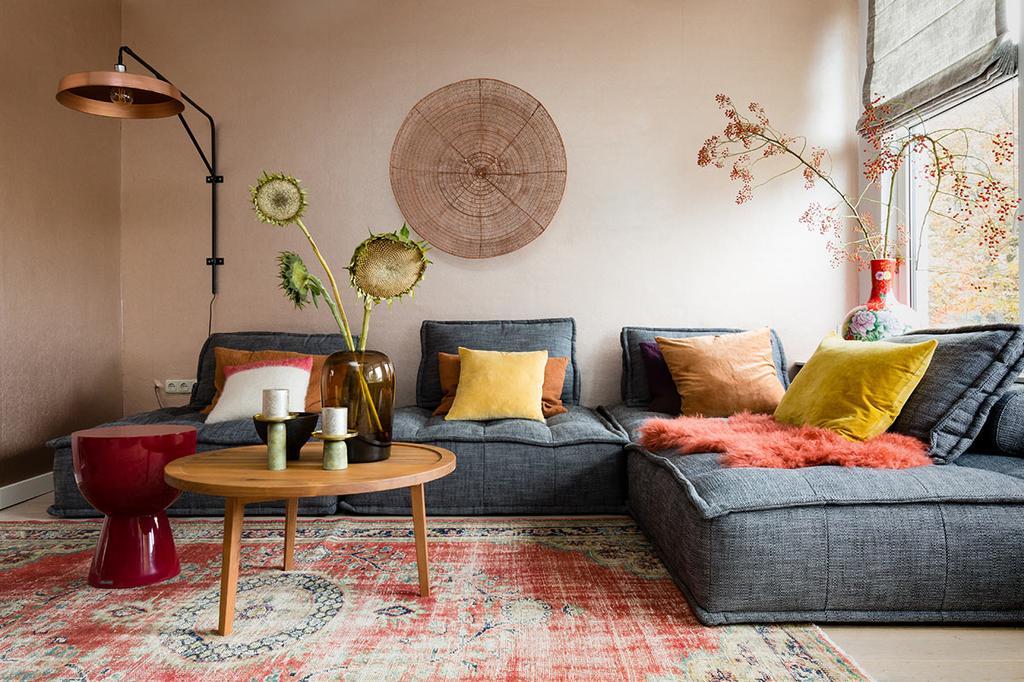 weer verliefd op je huis: roze wand in de zithoek met grijze loungebank