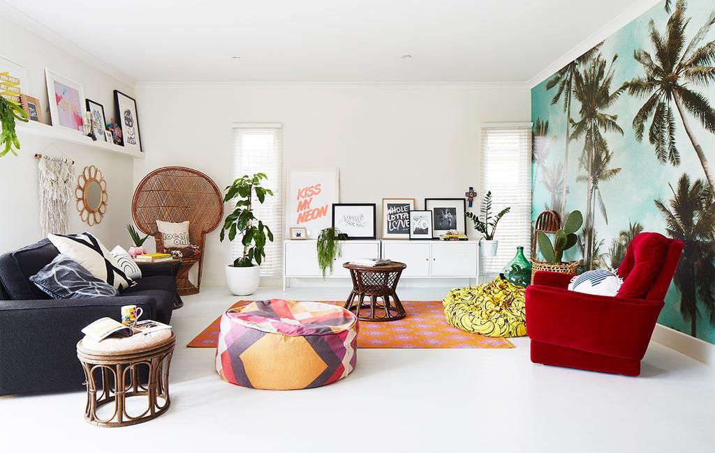 vtwonen binnenkijken special 07-2021 | de woonkamer met een behang met palmbomen, een rode stoel, een oranje vloerkleed, in de achtergrond staat er een pauwstoel