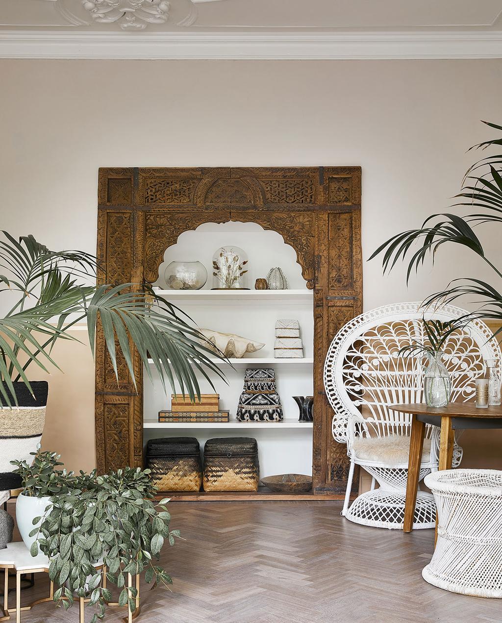 vtwonen 06-2021 | witte pauwstoel in de woonkamer met een kast met bijzondere wereldse woonaccessoires zoals vazen en manden