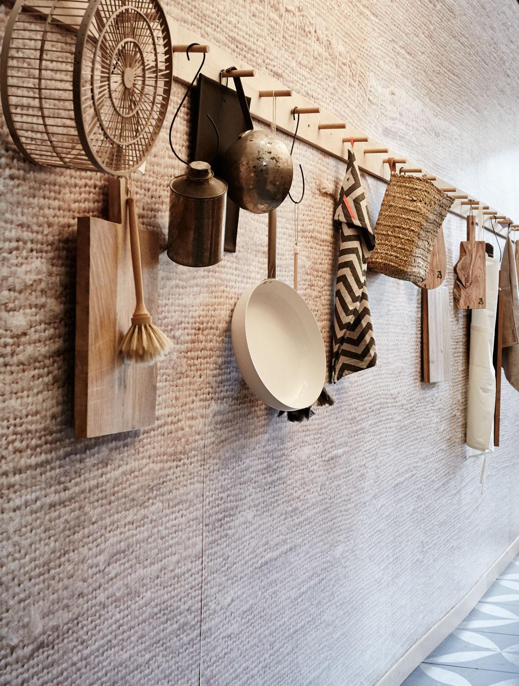 lange kapstok met geweven behang en keukengerei, snijplanken, pannen, borstels