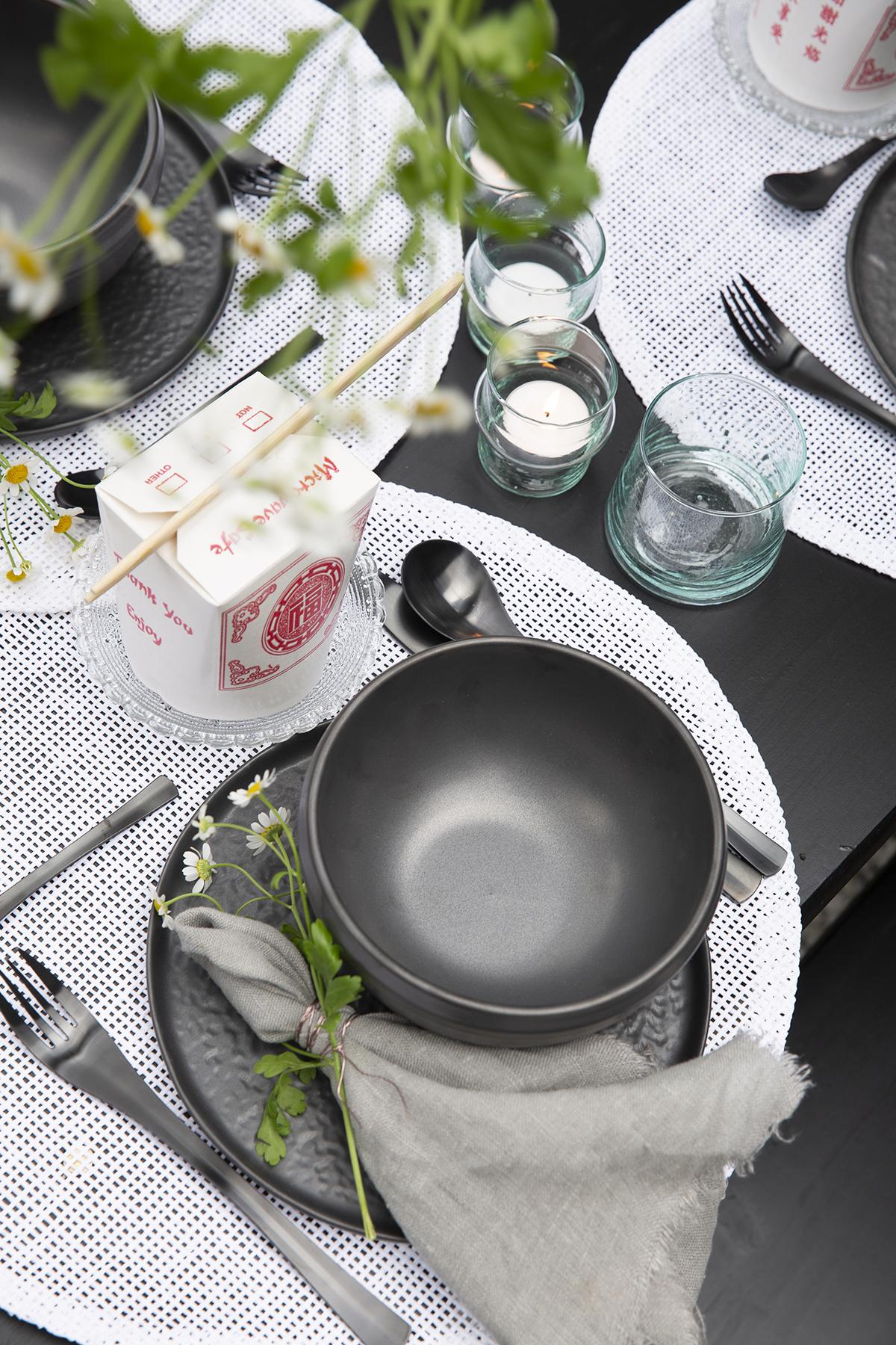 gestylde tafel met donker servies en bestek om buiten te eten