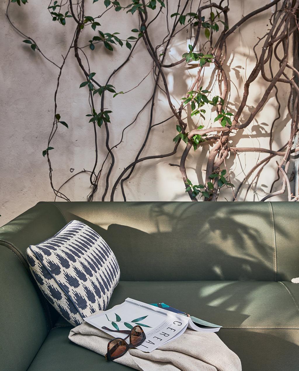 vtwonen 05-2021 | collectie buitenmeubels met een groene bank, kussen, zonnebril en magazine