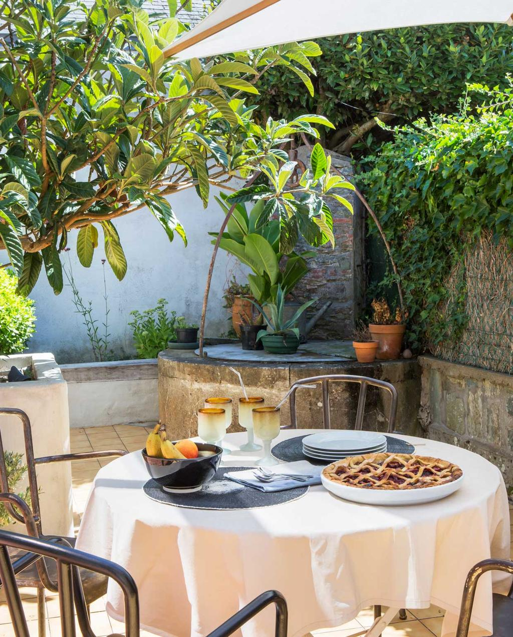 vtwonen binnenkijken special 07-2021 | binnenkijken in een vissershuis | terras met gedekte tafel met wit tafelkleed, metalen stoelen, een witte parasol en veel kleine bomen