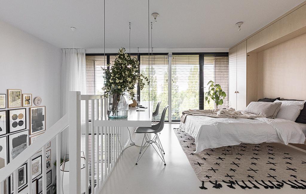 vtwonen 04-2021 | vide slaapkamer met vloerkleed en wit opgemaakt bed
