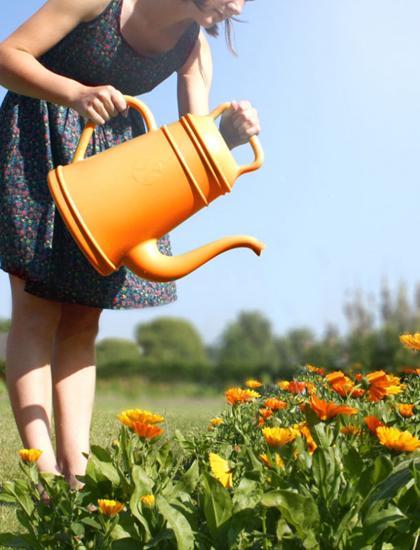 bloemen water geven met oranje gieter