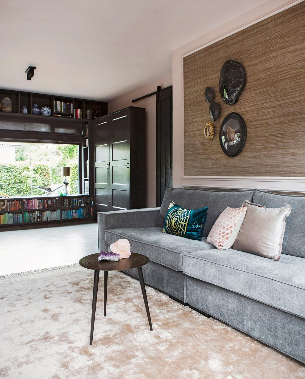 vtwonen 06-2021 | grijze bank in de woonkamer met een plaat op de muur en schilderijen