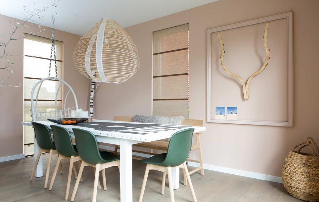roze eethoek met groene stoelen en een witte tafel