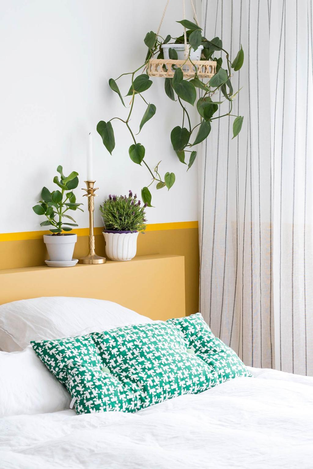 Wit bed, gele lambrisering en planten in de slaapkamer