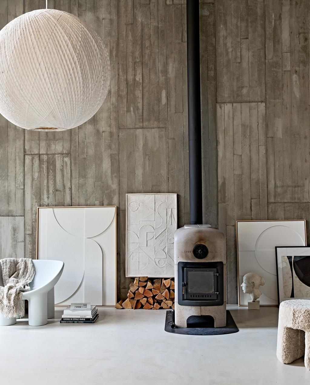 vtwonen 02-2021 | grote ronde lamp met verschillende kunstwerken met diepte, en houtkachel