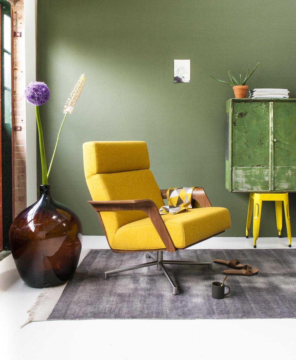 Gele stoel in een groen interieur als echte eyecatcher.