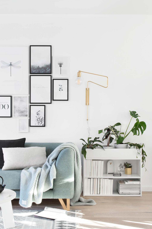 DIY boekenkast met een planten, een blauwe bank en schilderijen
