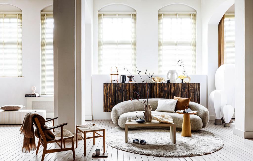 vtwonen 08-2021 | woonkamer met houten stoel en tafel en een grijze bank met een wit rond vloerkleed