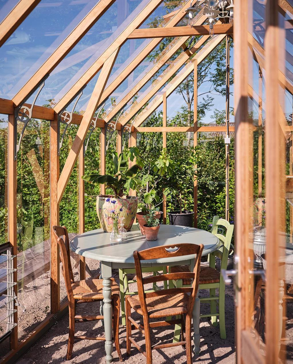 vtwonen tuin special 3 2021 | glazen overkapping met ronde tafel en houten stoelen