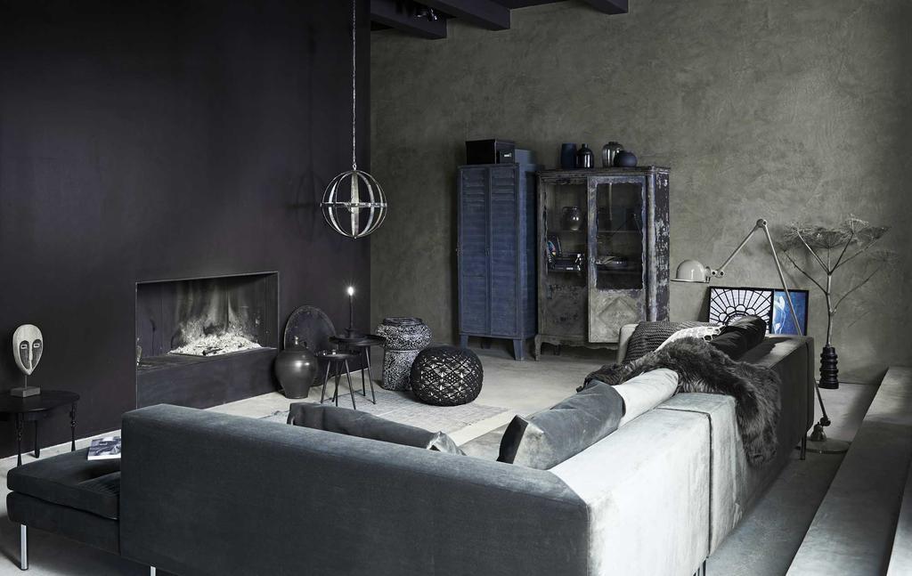 Een zwart interieur met zwarte haard en een grijze bank