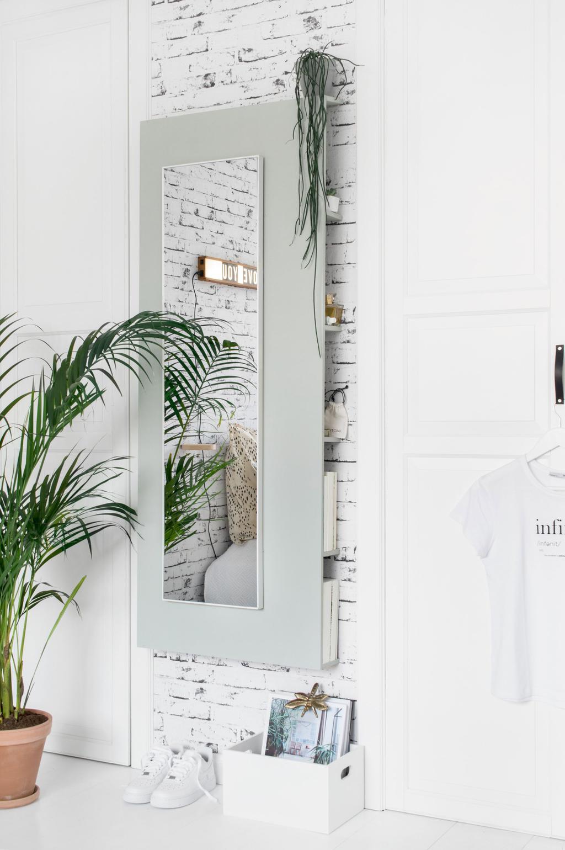 DIY spiegel met opbergruimte in een witte slaapkamer met planten
